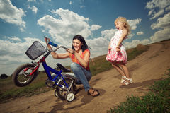 Mother teaching how to ride bicycle Royalty Free Stock Photos