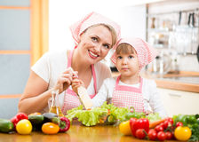 Mother teaching kid daughter mixing salad Royalty Free Stock Photo