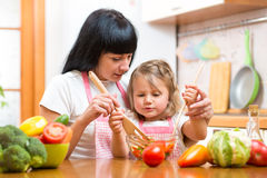 Mother teaching kid daughter mixing salad at kitchen. Mother teaching kid mixing salad at kitchen stock image