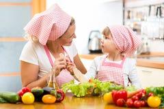 Mother teaching kid mixing salad at kitchen. Mother teaching kid daughter mixing salad at kitchen stock photos