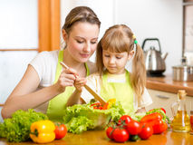 Mother teaching kid mixing salad at kitchen Stock Photo