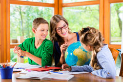 Mother teaching kids private lessons for school. Homeschooling mother teaching kids private lessons in geography Royalty Free Stock Image