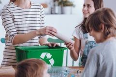 Mother teaching kids to segregate royalty free stock image