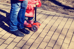 Mother teaching little daughter to ride scooter Stock Photo