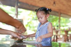 Mother teaching little girl for using Wooden rolling pin on Dough for pizza royalty free stock images