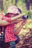 Mother teaching lovely asian daughter taking photos. Outdoors. Royalty Free Stock Photography