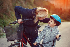 Mother teaching son cycling. At outdoor in sunset Stock Image