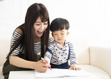 Mother teaching son draw and write at home stock photography
