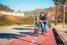 Mother teaching son to ride a bike in cycleway Stock Images