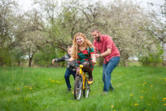 Mother teaching son to ride a bike by his example Stock Photo