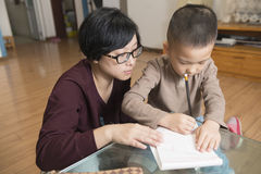 Mother teaching son writing Stock Photography