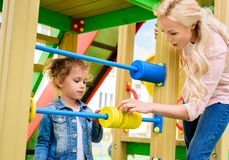 Mother teaching to count little daughter on abacus. At playground royalty free stock image
