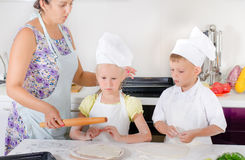 Mother teaching two children to bake Royalty Free Stock Photo