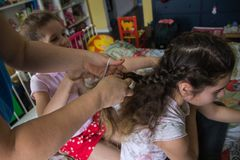 Mother teaching young girl braiding her friends hair royalty free stock image
