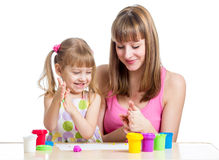 Mother teeaching kid to use play clay Stock Photo