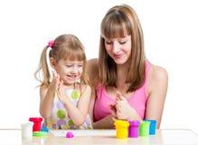 Mother teeaching kid to use play clay Stock Photo