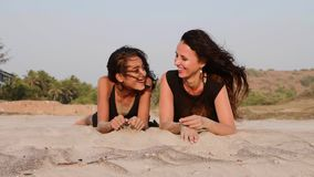 Mother and teen daughter lying together on the sandy beach, talking and laughing stock footage