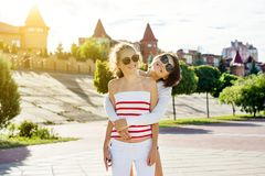 Mother and teen daughter portrait. Background of the summer city. Mom and daughter hug and laugh Stock Photography