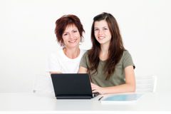 Mother teen homework. Middle aged mother helping teen daughter studying homework Royalty Free Stock Images