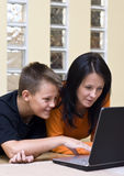 Mother and teenage boy with laptop. Mother and her teenage boy lying down on the floor of the living room, using a laptop computer together Stock Images