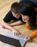 Mother and teenage boy with laptop. Mother and her teenage boy lying down on the floor of the living room, using a laptop computer together Stock Photos