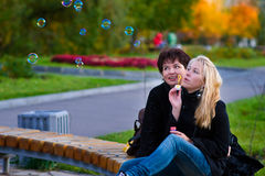 Mother and teenage daughter_2. Teenage daughter blow bubbles, her mom was watching her Stock Image