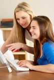 Mother And Teenage Daughter At Home Using Computer Royalty Free Stock Photo