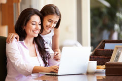 Mother And Teenage Daughter Looking At Laptop Together Stock Image