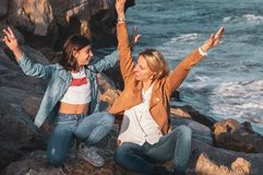 Mother and daughter sitting on the rocks by the mediterranean sea with arms raised playing with the air stock photography