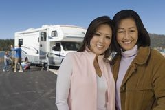 Mother and teenage daughter standing outside of RV at lake Royalty Free Stock Photo