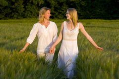 Mother and teenage daughter walking through barley field stock photo