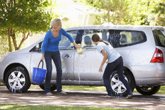 Mother And Teenage Daughter Washing Car Together Royalty Free Stock Photography