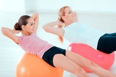 Mother and teenage girl at sports club. Fitness every day. Closeup side view image of beautiful teenage girl and her mother in sports clothing training on royalty free stock photos