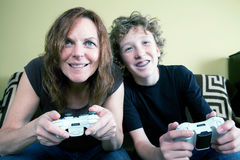 Mother and teenage son play video game together Stock Images
