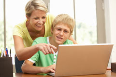 Mother And Teenage Son Using Laptop At Home. Smiling together Royalty Free Stock Photos