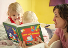 Mother tell tale in bed to her children Stock Photography