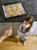 Mother telling daughter that she cannot have cookies. Photo of a young girl angry because her mother is telling her she cannot have any chocolate chip cookies stock images