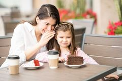 Mother telling a secret to her daughter at restaurant Stock Image