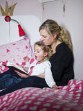 Mother tells a story to her daughter Stock Photos