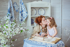 Mother thanks her little daughter for a help to her. On a kitchen. Their noses is dirty at a flour Stock Photo