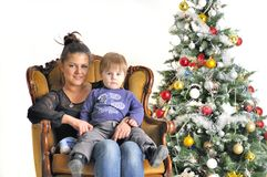 Mother and their small child sits on chair near Christmas tree Stock Photography