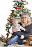 Mother and their small child sits near Christmas tree with teddy bear Stock Photography