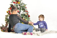Mother and their small child sits near Christmas tree with toy Royalty Free Stock Photos