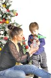 Mother and their small child sits near Christmas tree with toy Royalty Free Stock Image