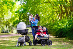 Mother with three children in buggy and stroller Stock Photos