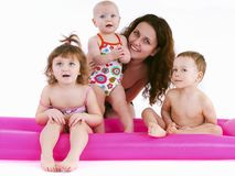 Mother with three children in swimsuits Stock Photos