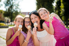 Mother with three daughters eating ice cream. Fun day outdoor. Stock Images