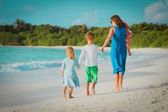 Mother with three kids walk on beach stock images