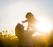 Mother throwing baby girl in air at the rapeseed field Stock Image