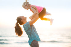 Mother throwing baby up on beach in the evening Stock Photo